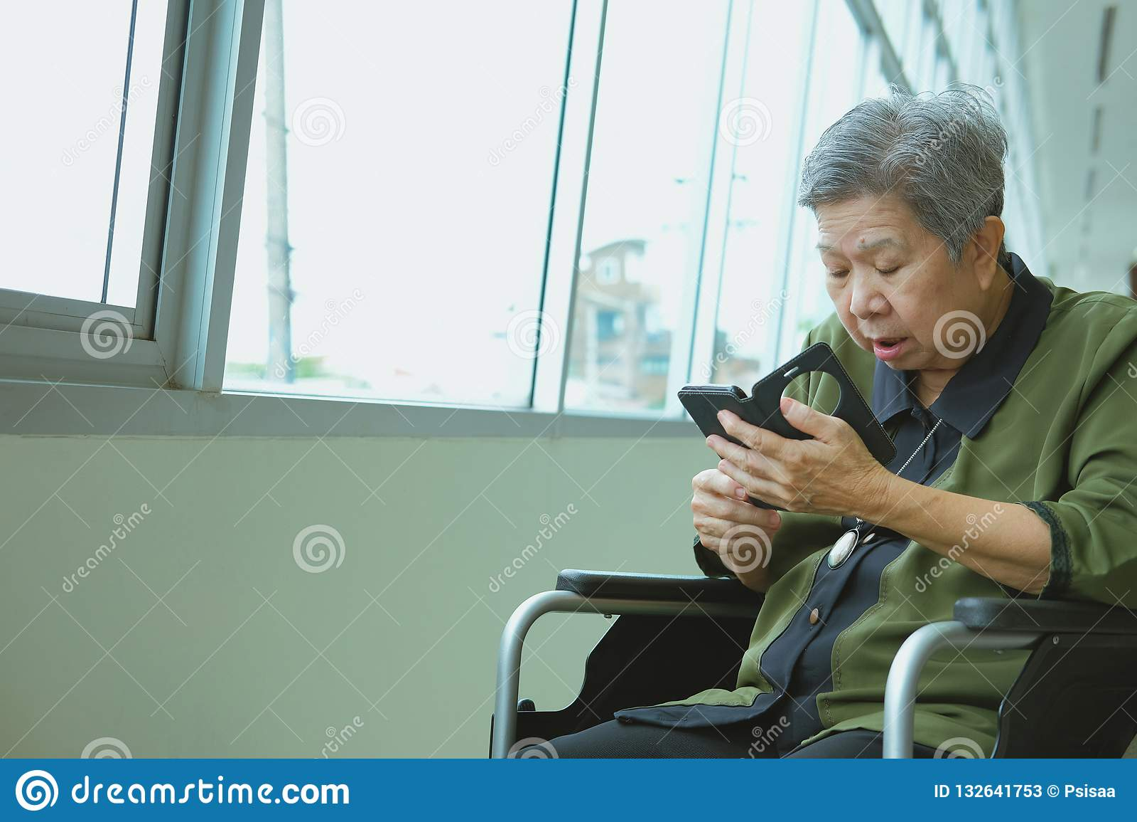 elder woman in wheelchair holding mobile phone surprised shocked