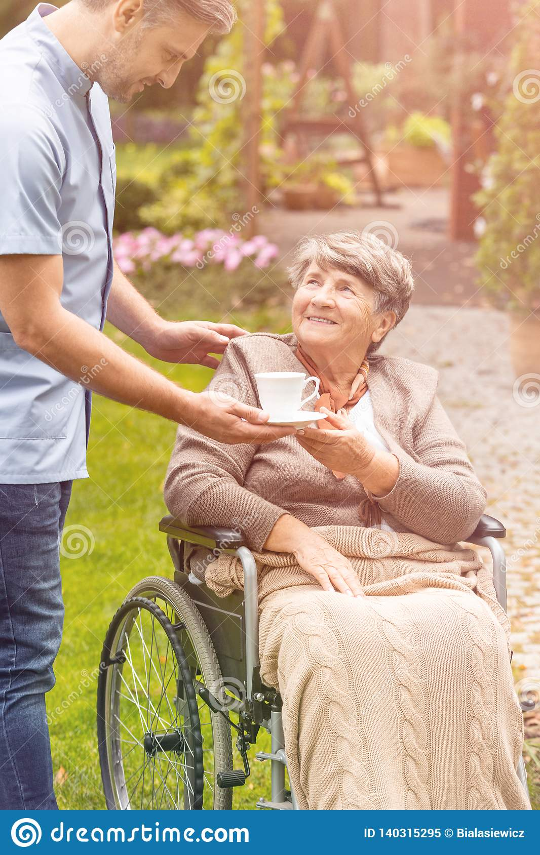 Elder woman in a wheelchair taking a cup of tea from a nurse