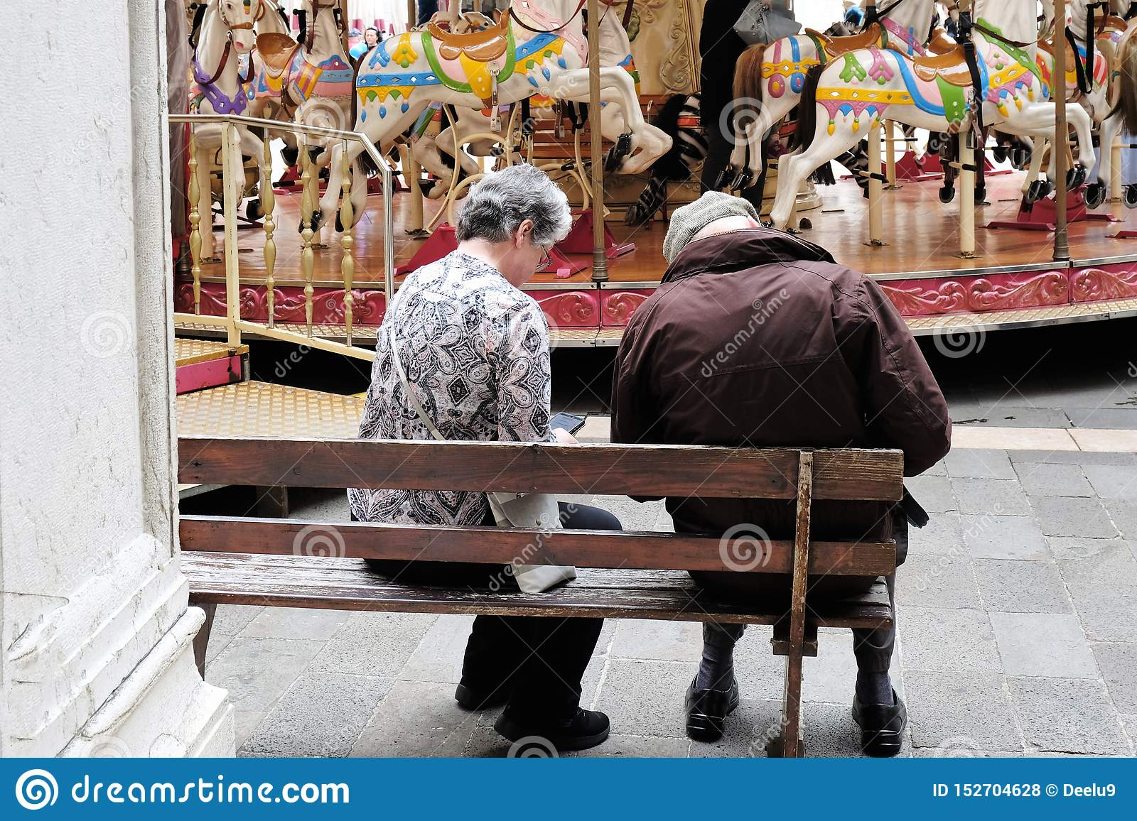 Elderely couple resting on bench in front of merry go round in Treviso, Italy