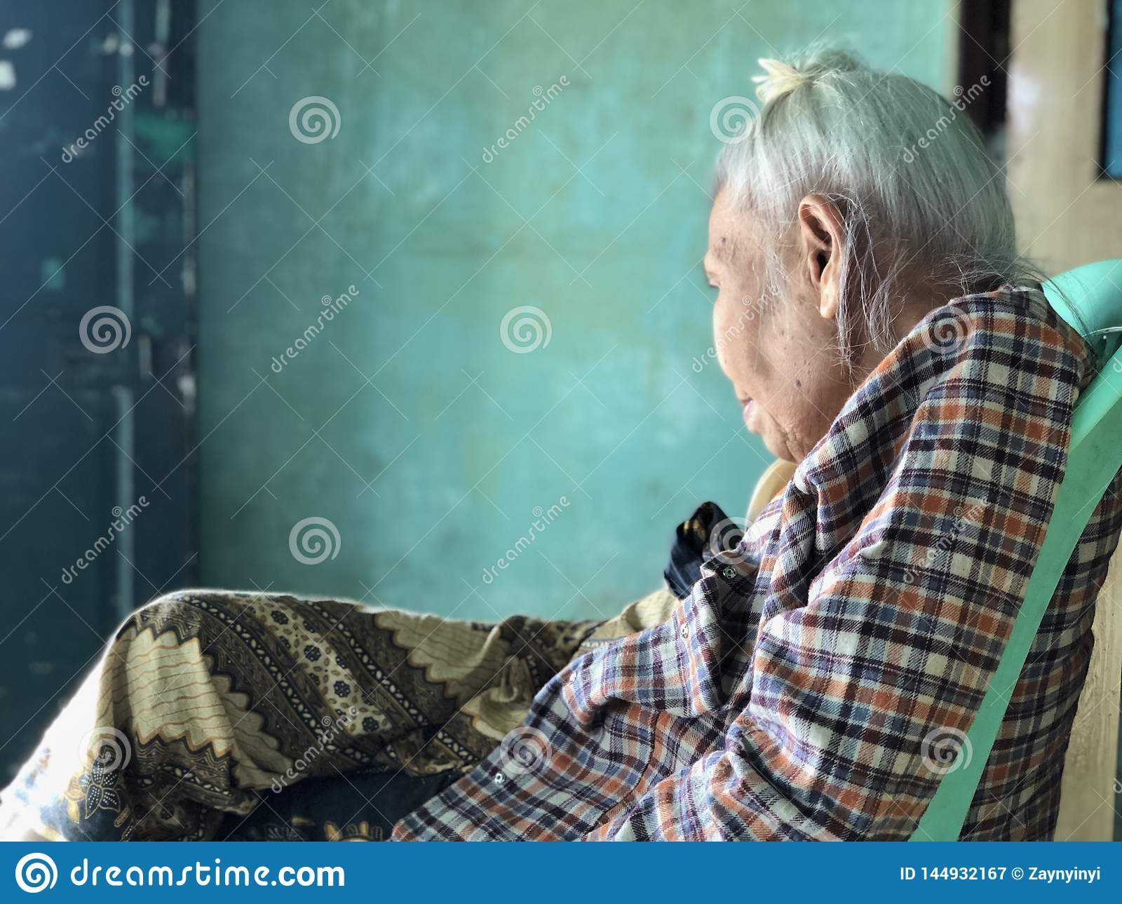 Elderly Asian, Burmese Woman siting with leg crossed on green plastic chair and gazing at distance