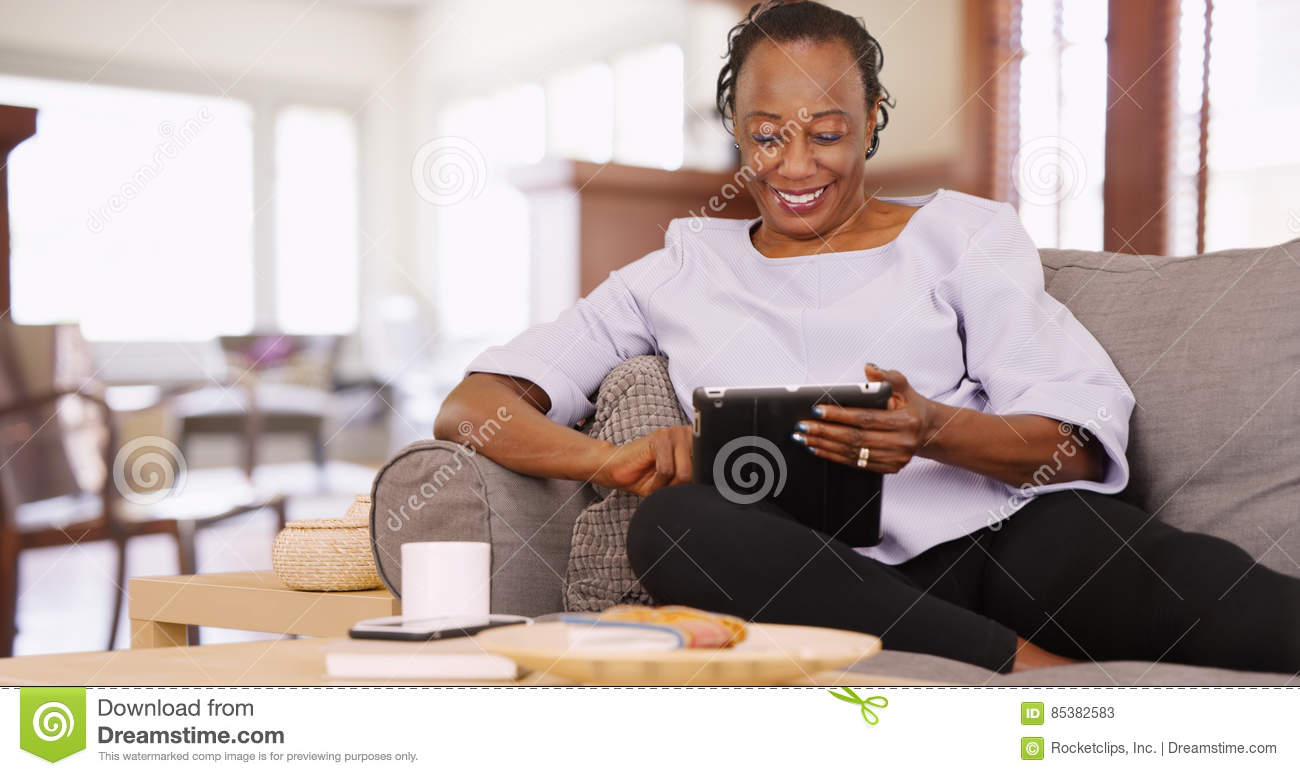 An elderly black woman uses her tablet while relaxing on the couch
