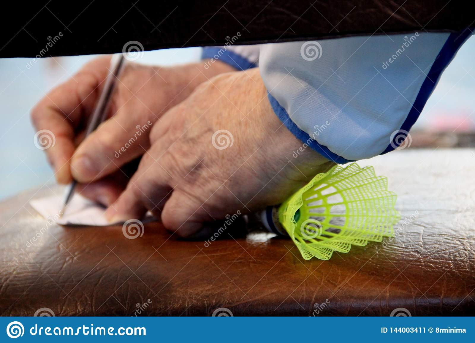 an older trainer takes notes with a shuttlecock for badminton in his fist, framing close-up