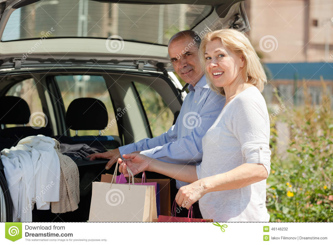 Elderly couple bringing bags to the trunk of his car