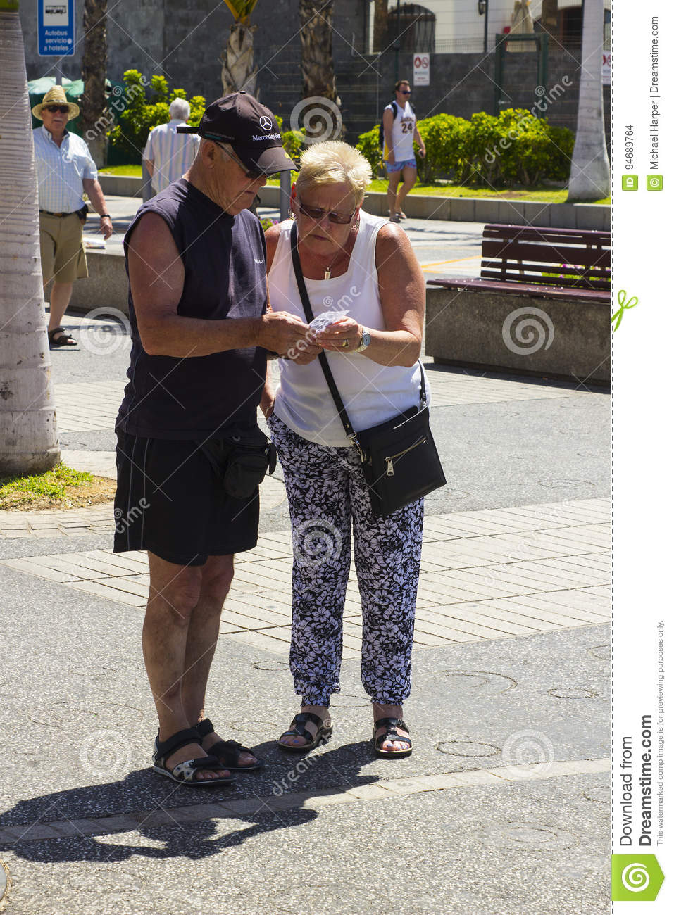 An elderly couple check a till receipt on the the main street of Playa Las Americas in Teneriffe
