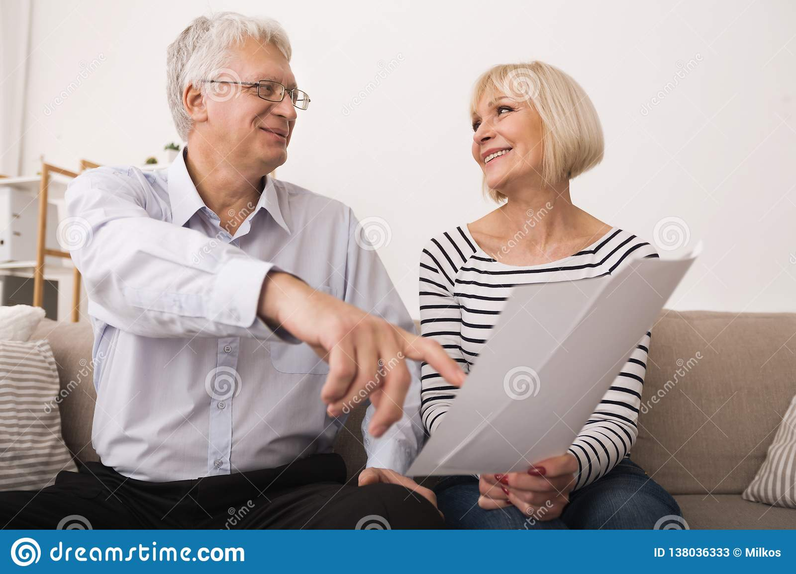 Elderly couple discussing documents, looking at each other