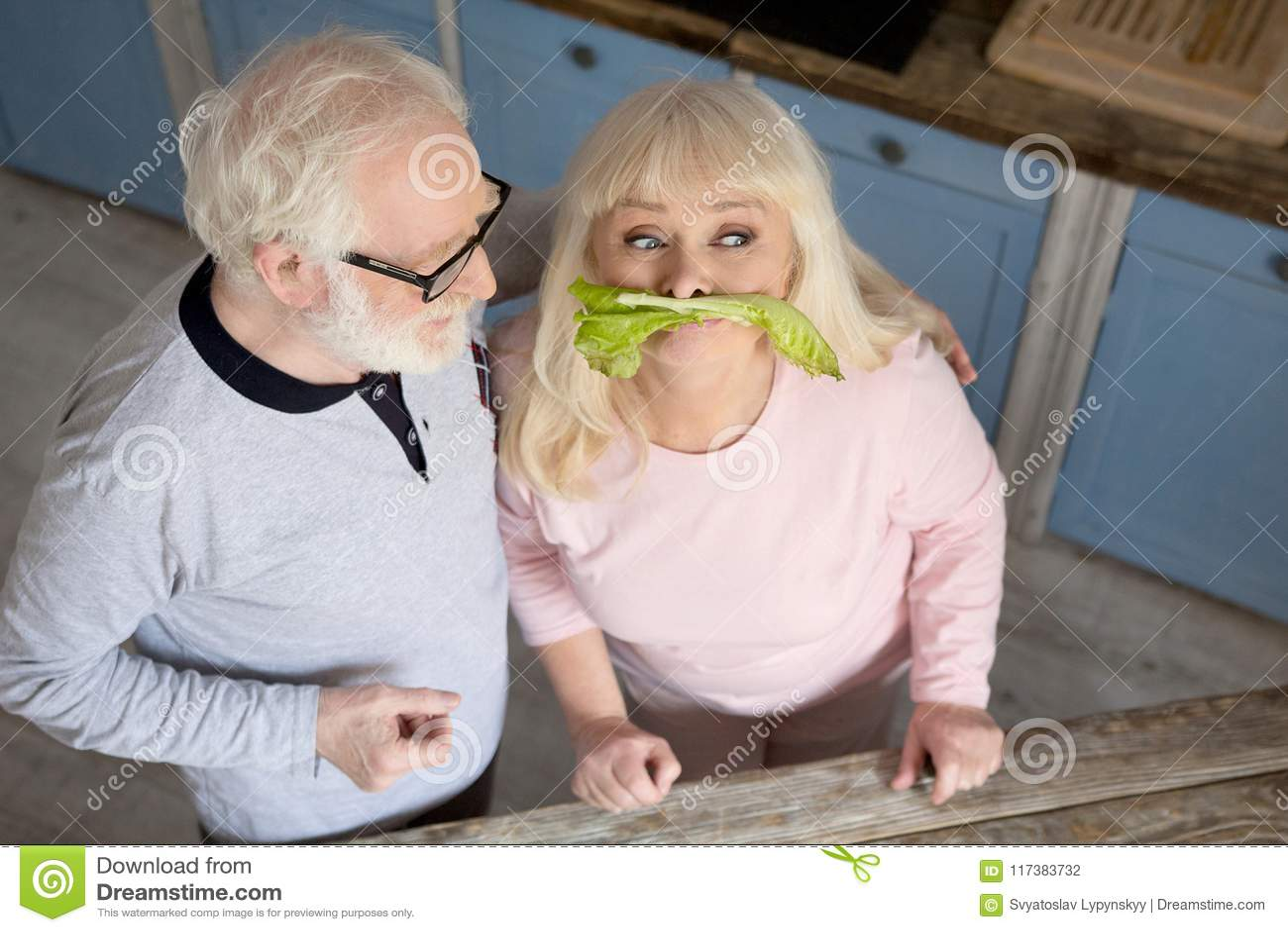 Elderly Couple Having Fun In Kitchen Stock Photo Image Of