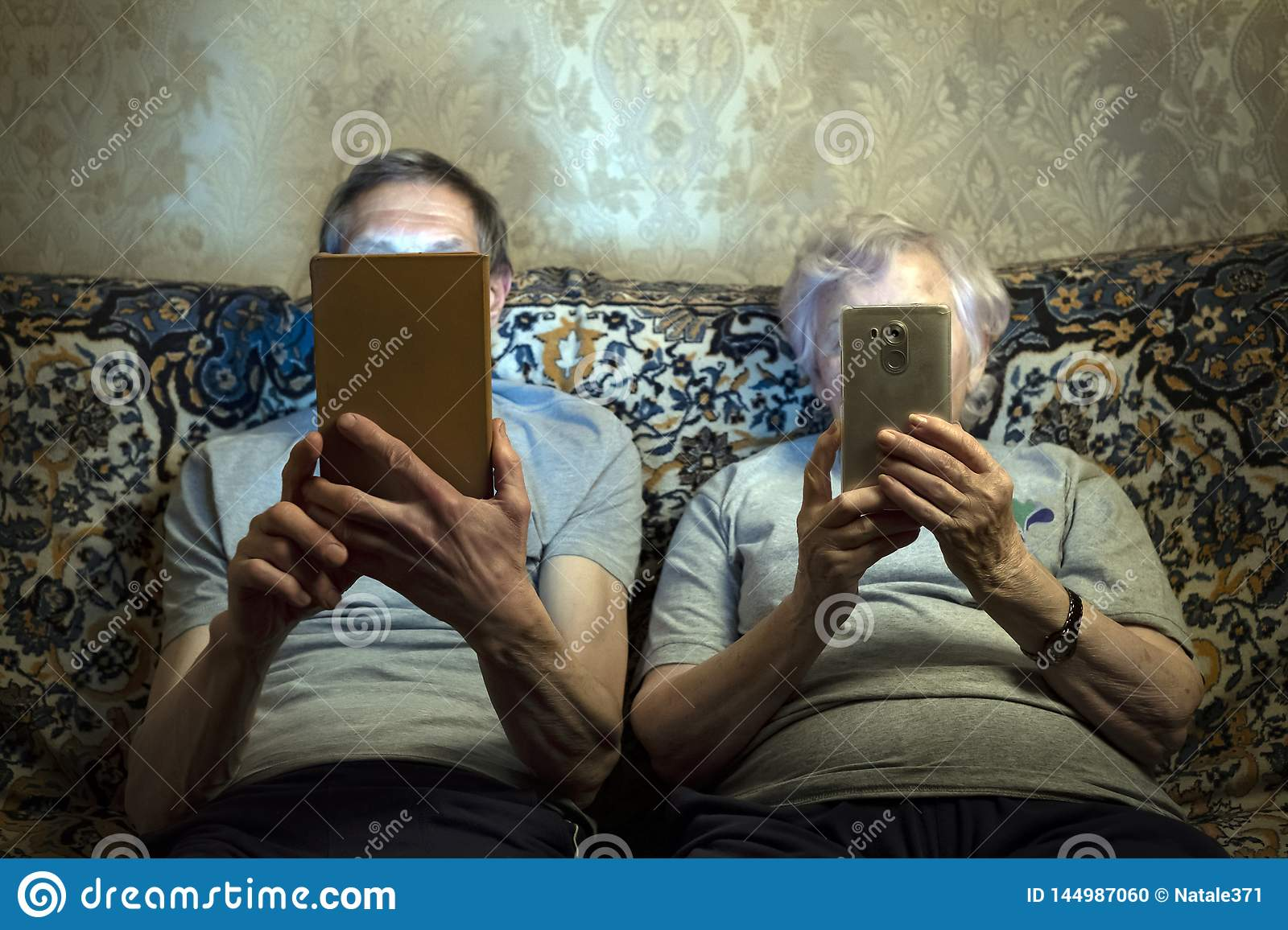 An elderly couple sit on the couch with gadgets, look at them close their faces.