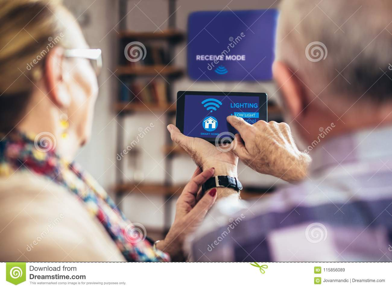 Elderly couple sitting comfortably on a sofa with their backs holiding remote control home system