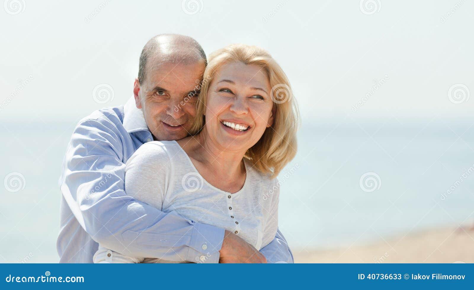 Elderly couple walking on the beach in summer