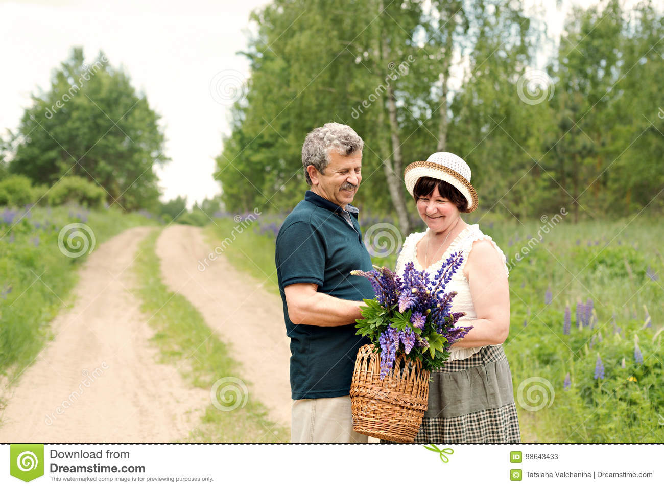 An elderly couple walks through the forest and a man gives a woman a woven basket with a bouquet of flowers of purple lupines