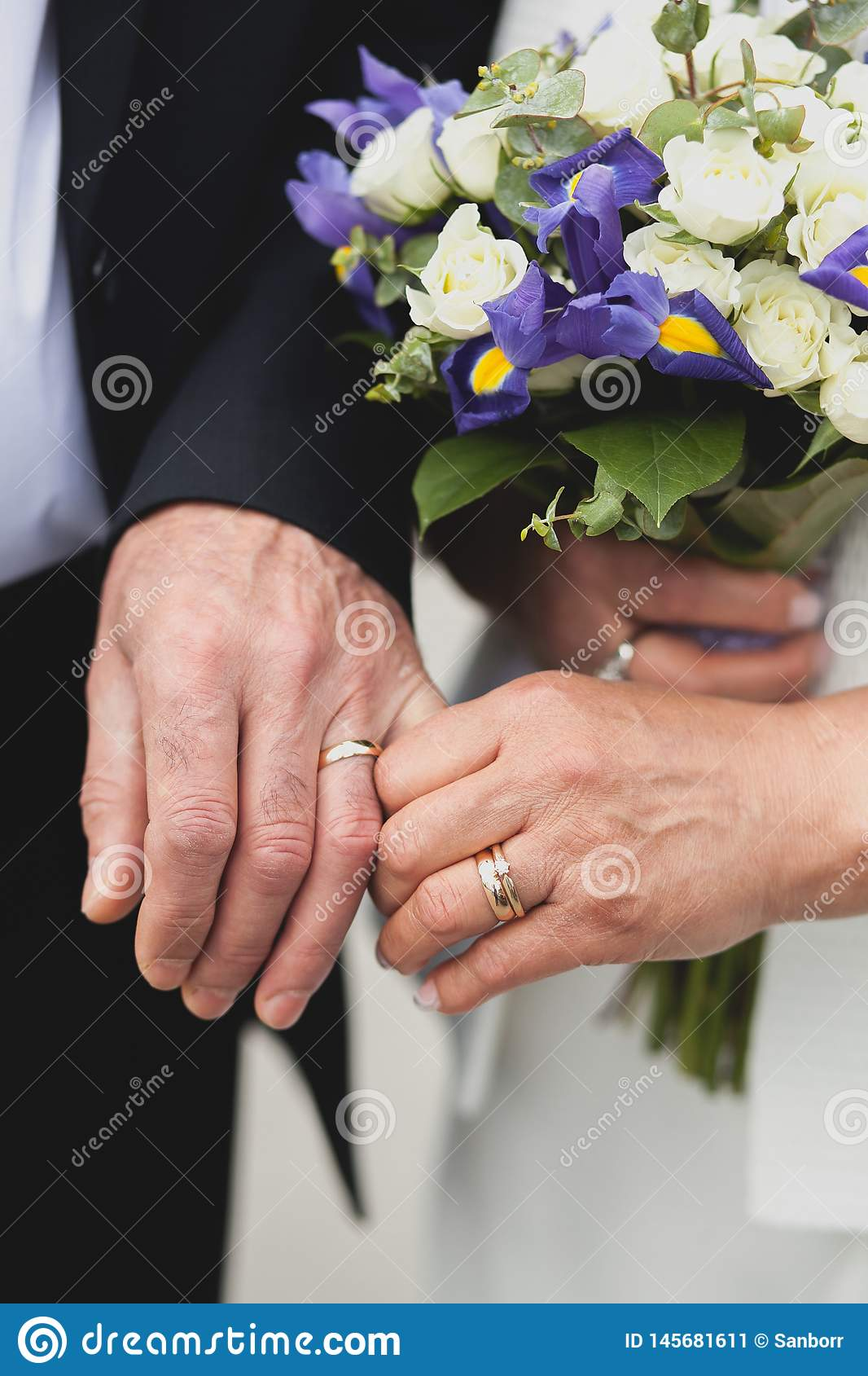 An elderly couple after the wedding in the Church, their hands close-up. Wedding of the elderly, the bride holds a beautiful
