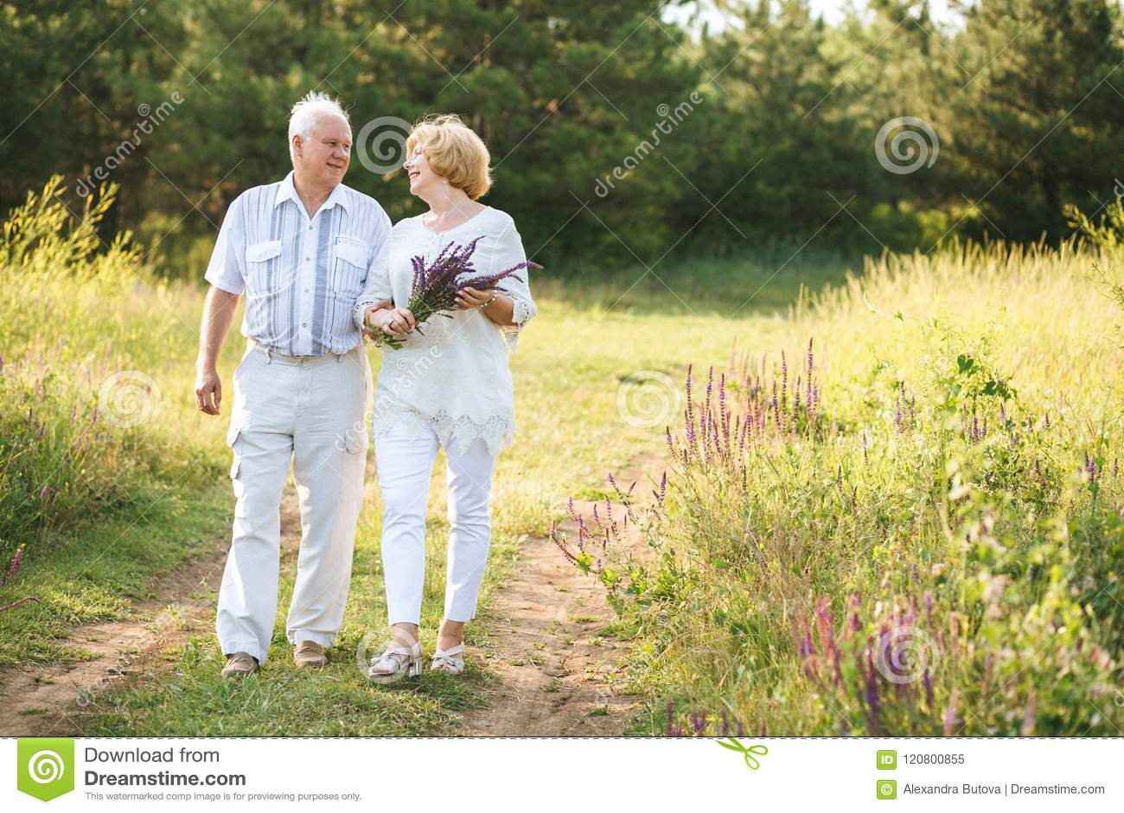 953de40a4ae4 Elderly Couple In The White Linen Dress Walking Outdoors