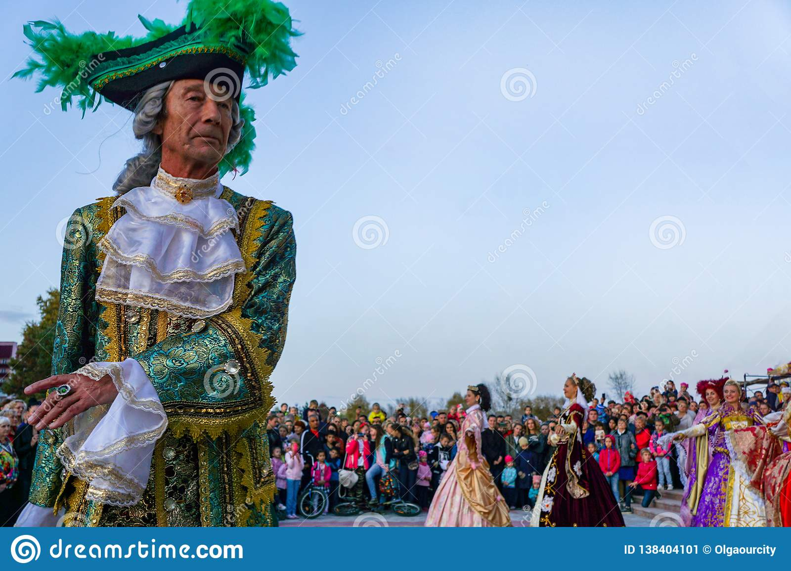 Elderly dancers in bright historical medieval costumes, dancing in the square in summer