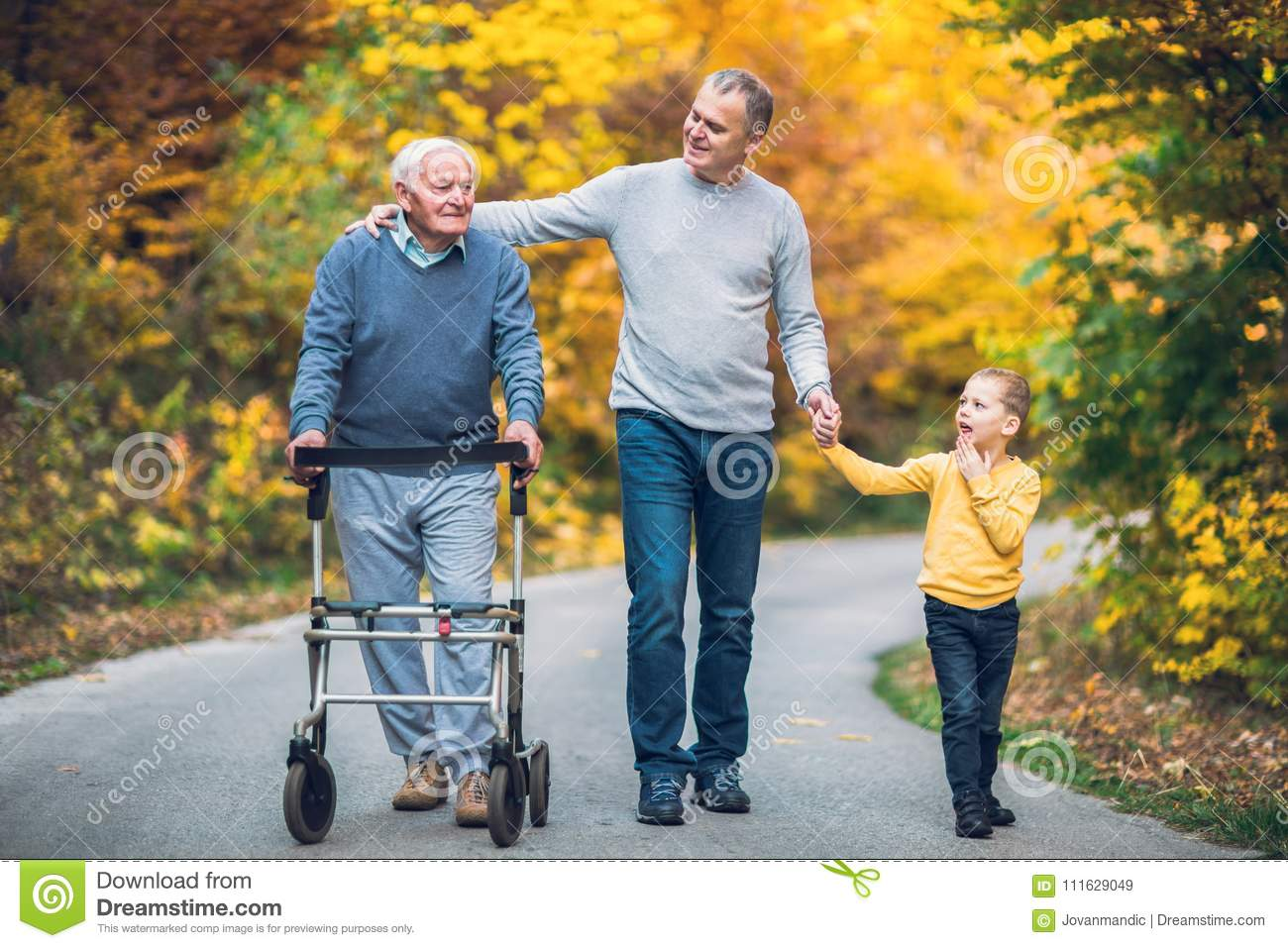 Elderly father, adult son and grandson out for a walk in the park