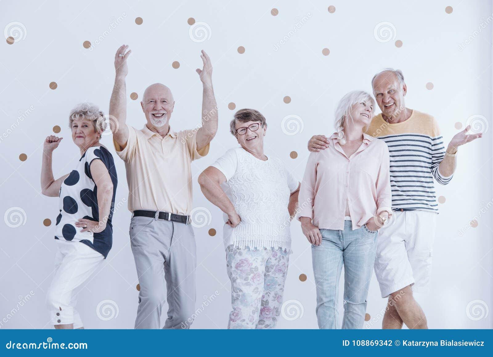 Elderly friends dancing and talking