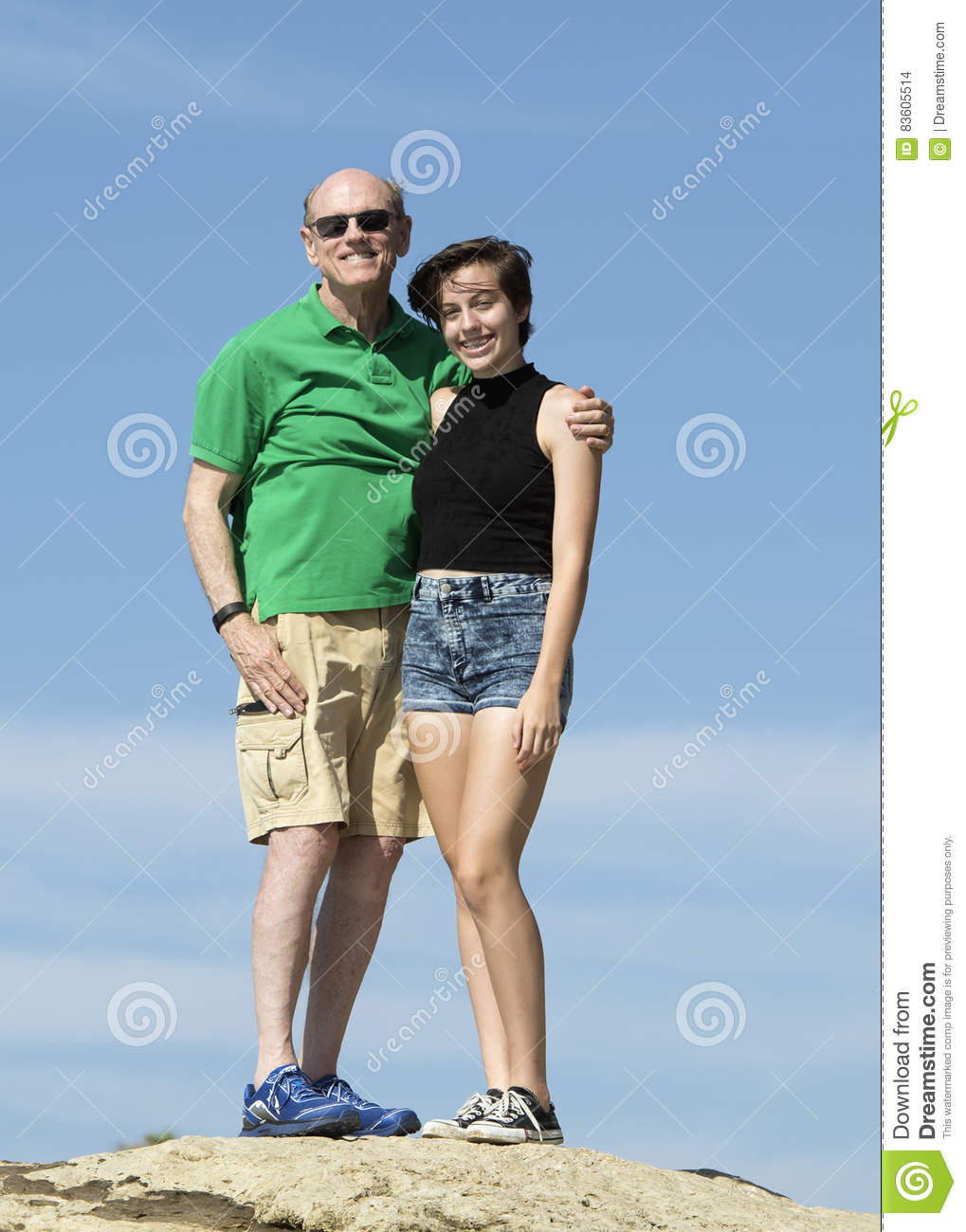 Elderly grandfather and teenage granddaughter standing on a rock