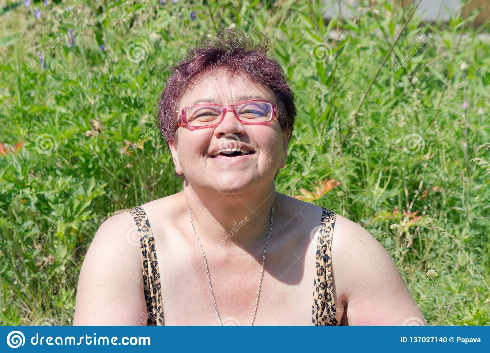 Elderly happy woman with glasses sunbathes in the grass under the bright summer sun