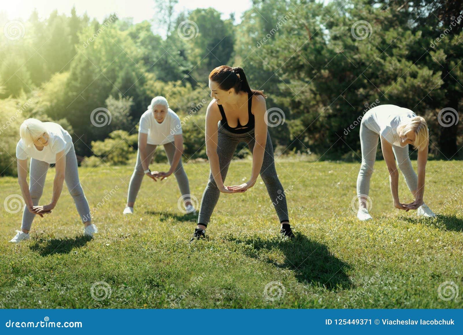 Elderly ladies stretching backs during group workout