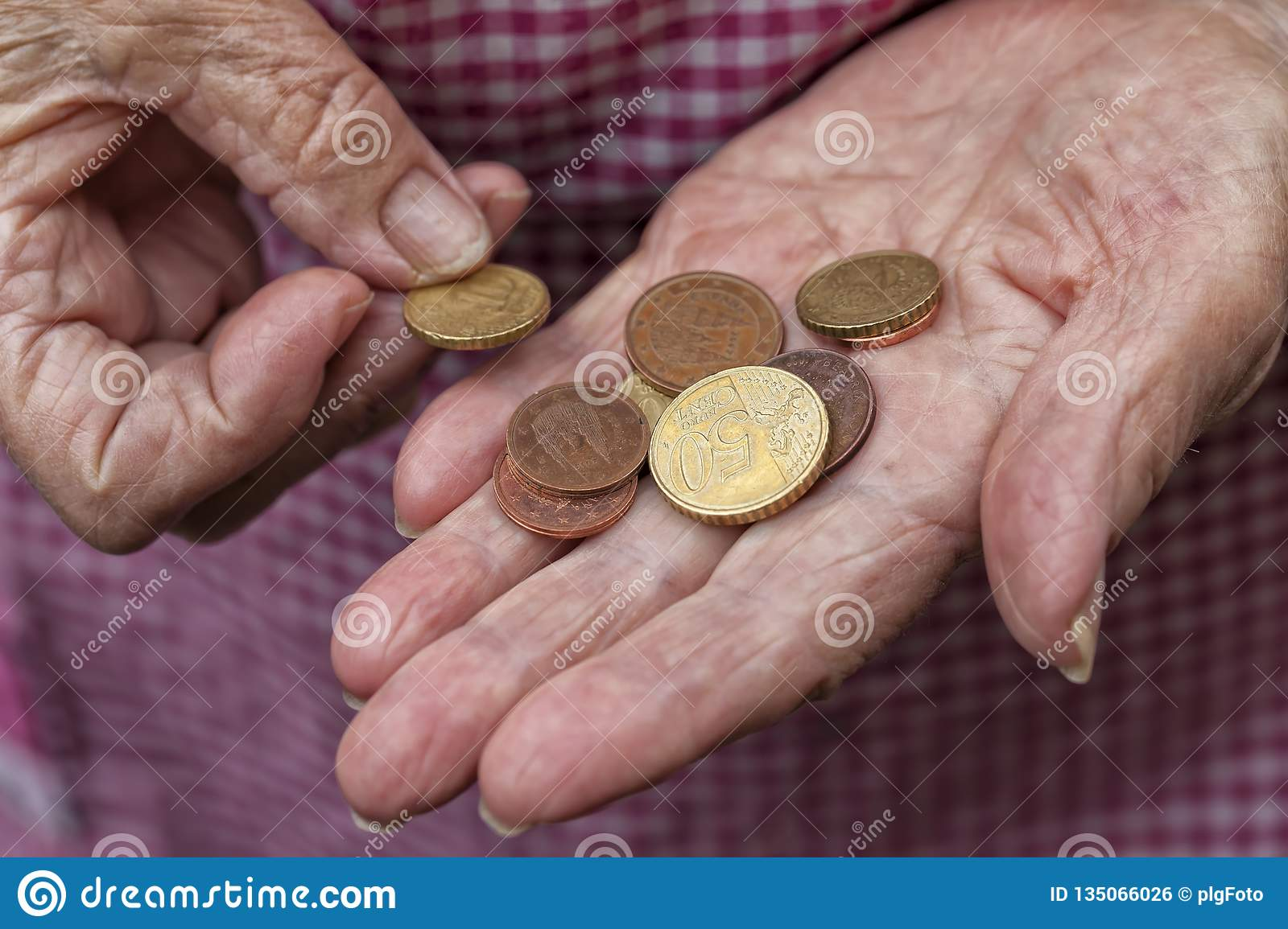 An elderly lady holds a few cents of euro