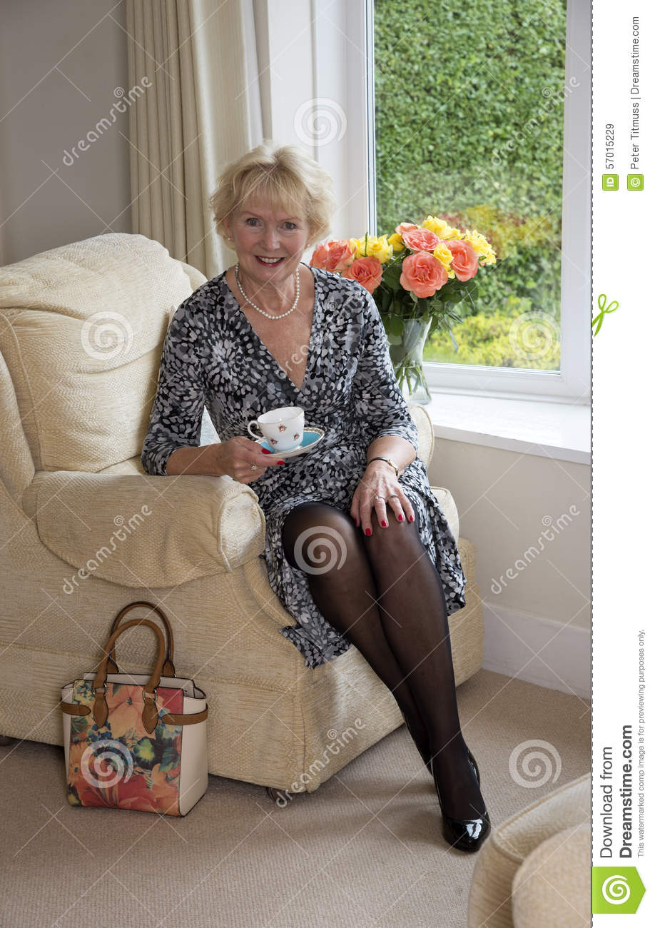Elderly Lady Sitting In A Chair Drinking Tea Stock Photo