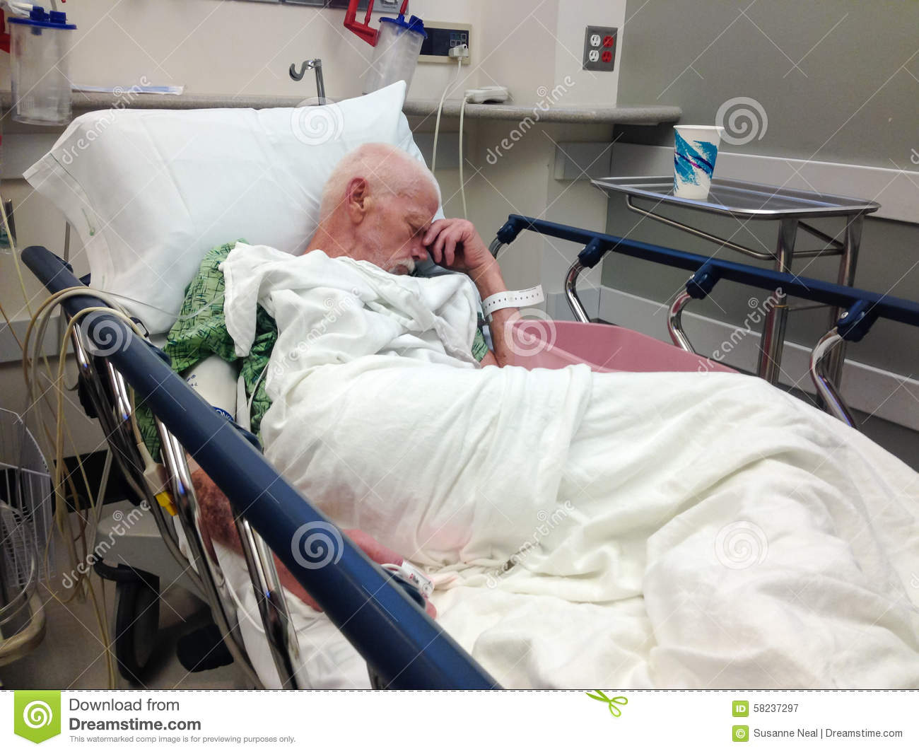 elderly male hospital patient in hospital bed stock image