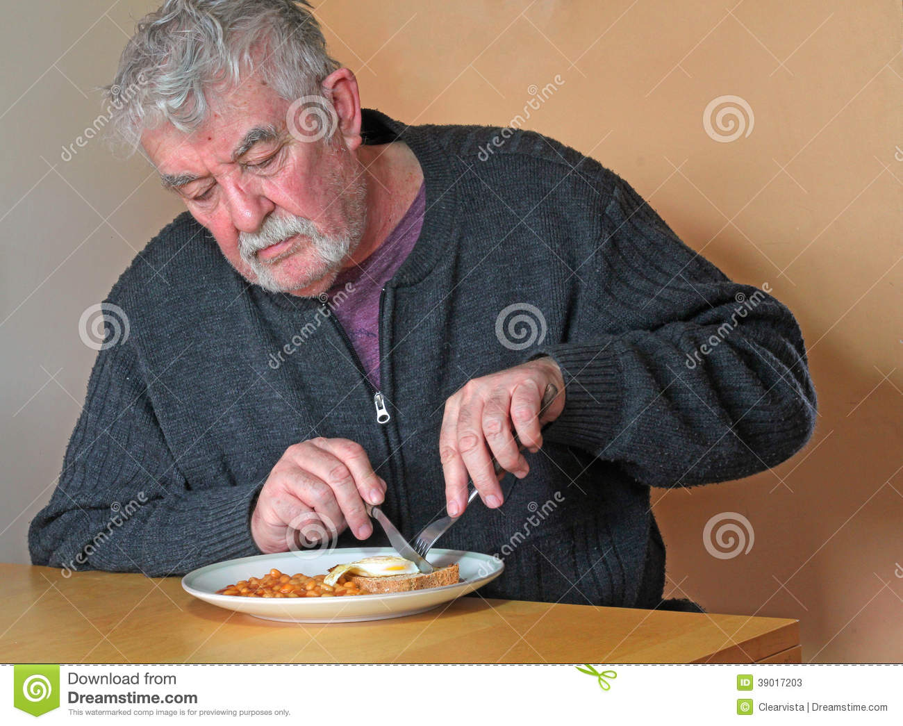 elderly man eating at a table  stock image