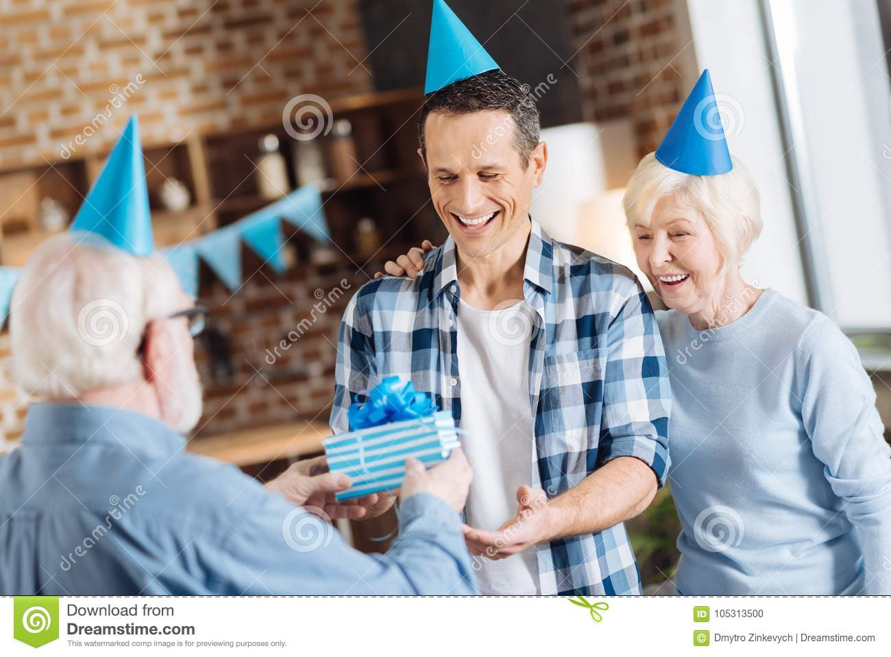 Pleasant Elderly Men Giving A Birthday Present To His Adult Son While The Mother Hugging Him And All Of Them Are Wearing Party Hats