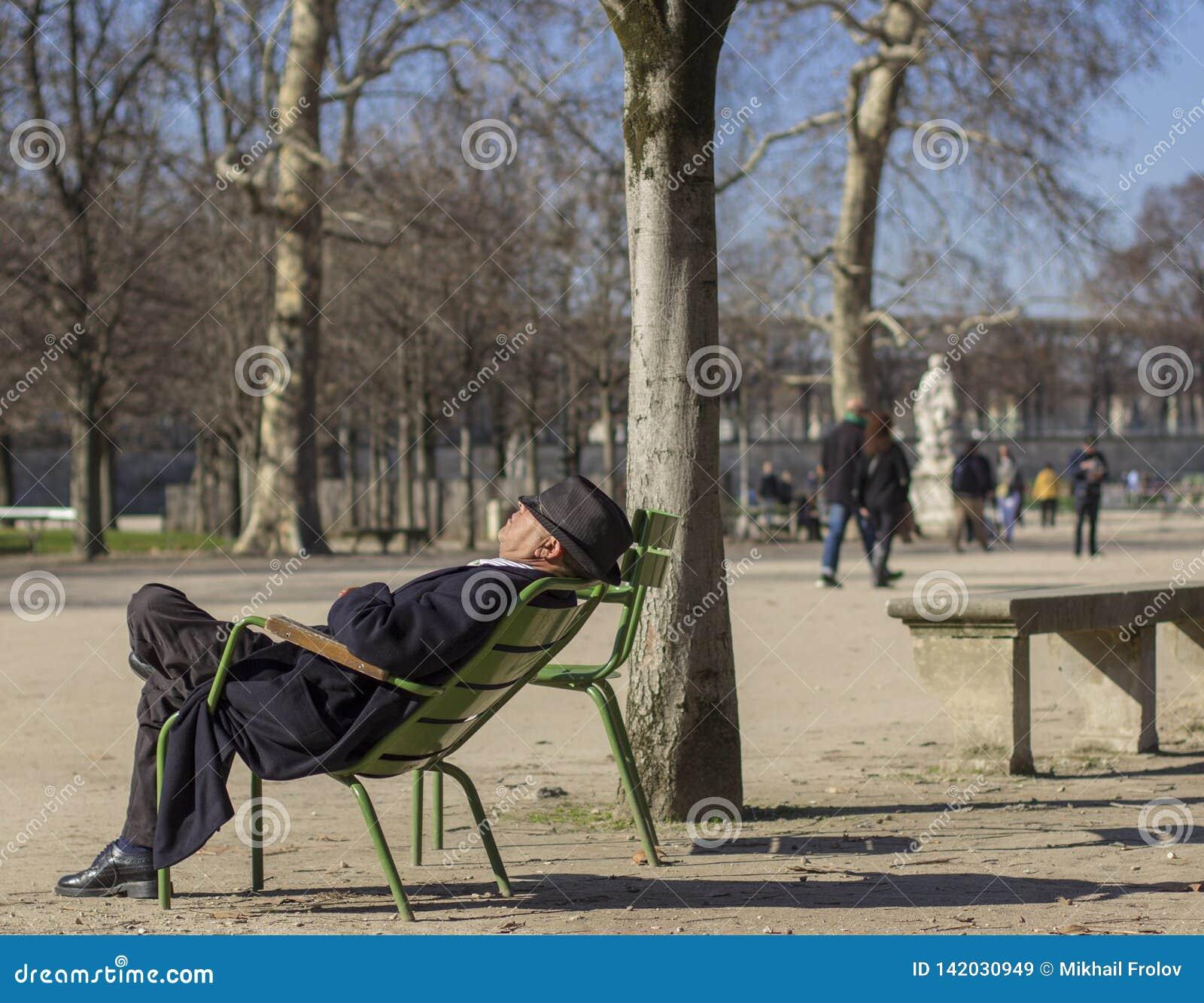 An elderly man in a hat is sleeping in the sun in the park