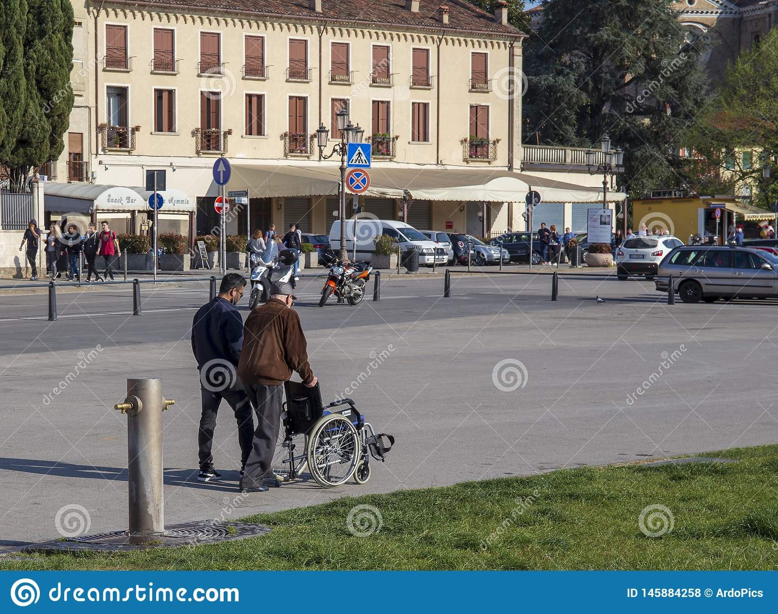 Elderly man helped by a boy, he pushes the wheelchair