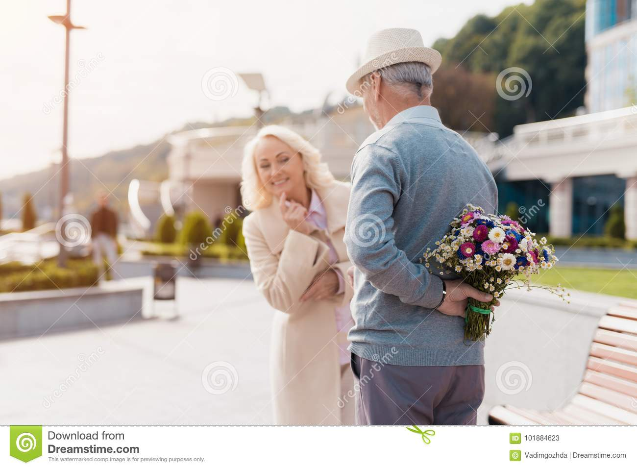 An elderly man is holding a bouquet of flowers behind back a woman an elderly man is holding a bouquet of flowers behind back a woman came on izmirmasajfo