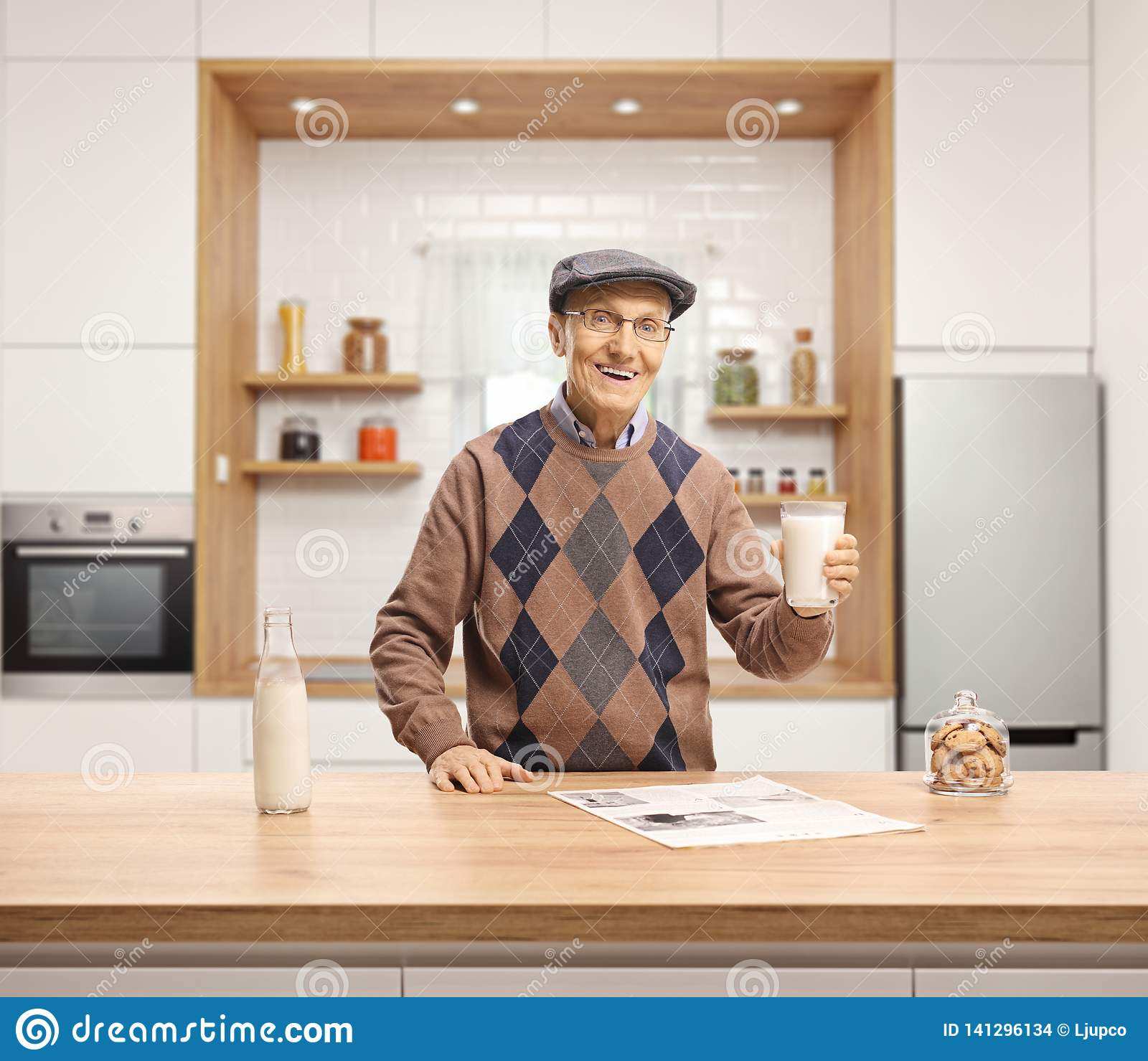 Elderly man holding a glass of milk and standing behind a wooden counter in a kitchen