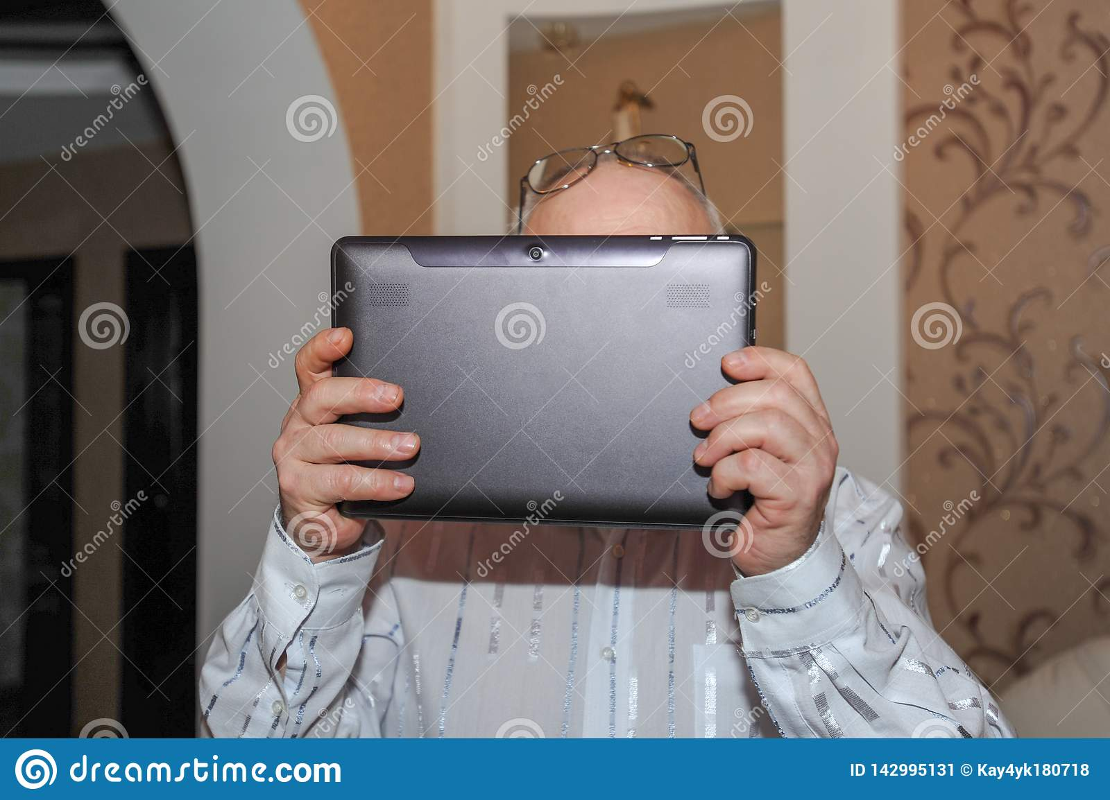 Elderly man holding tablet on lap, planning and booking retirement trip, closeup. using a tablet in his house