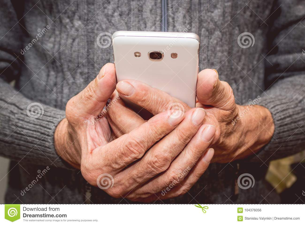 Elderly man standing with mobile phone in hand