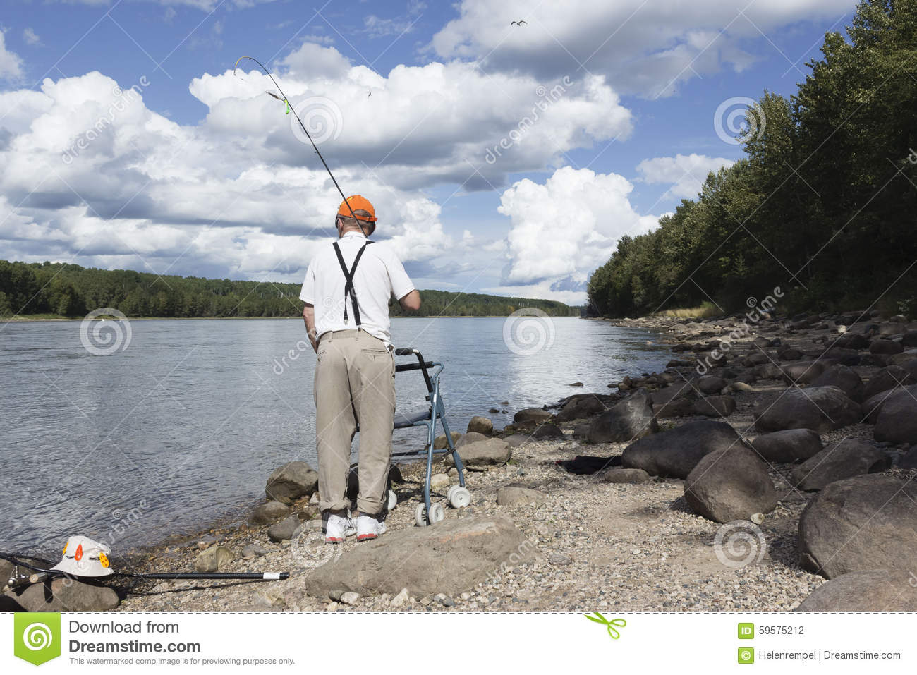 Elderly man walking along the shore line with walker and a for Senior fishing license