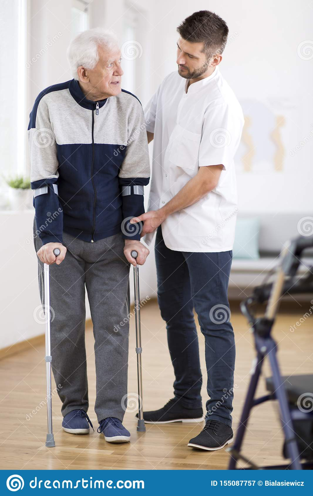 Elderly man walking on crutches and a helpful male nurse supporting him