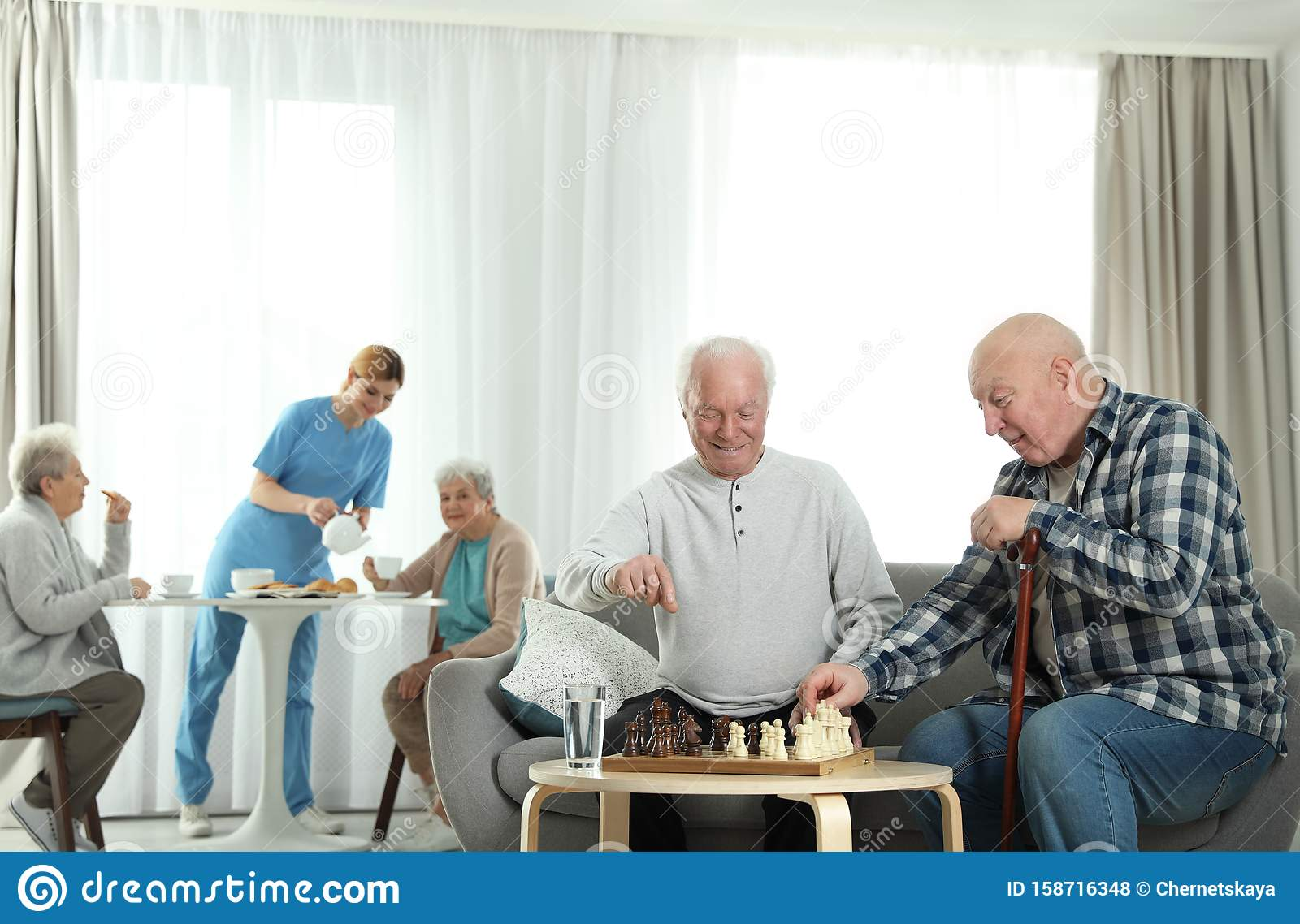 Elderly men playing chess while nurse serving breakfast to women. Assisting senior people