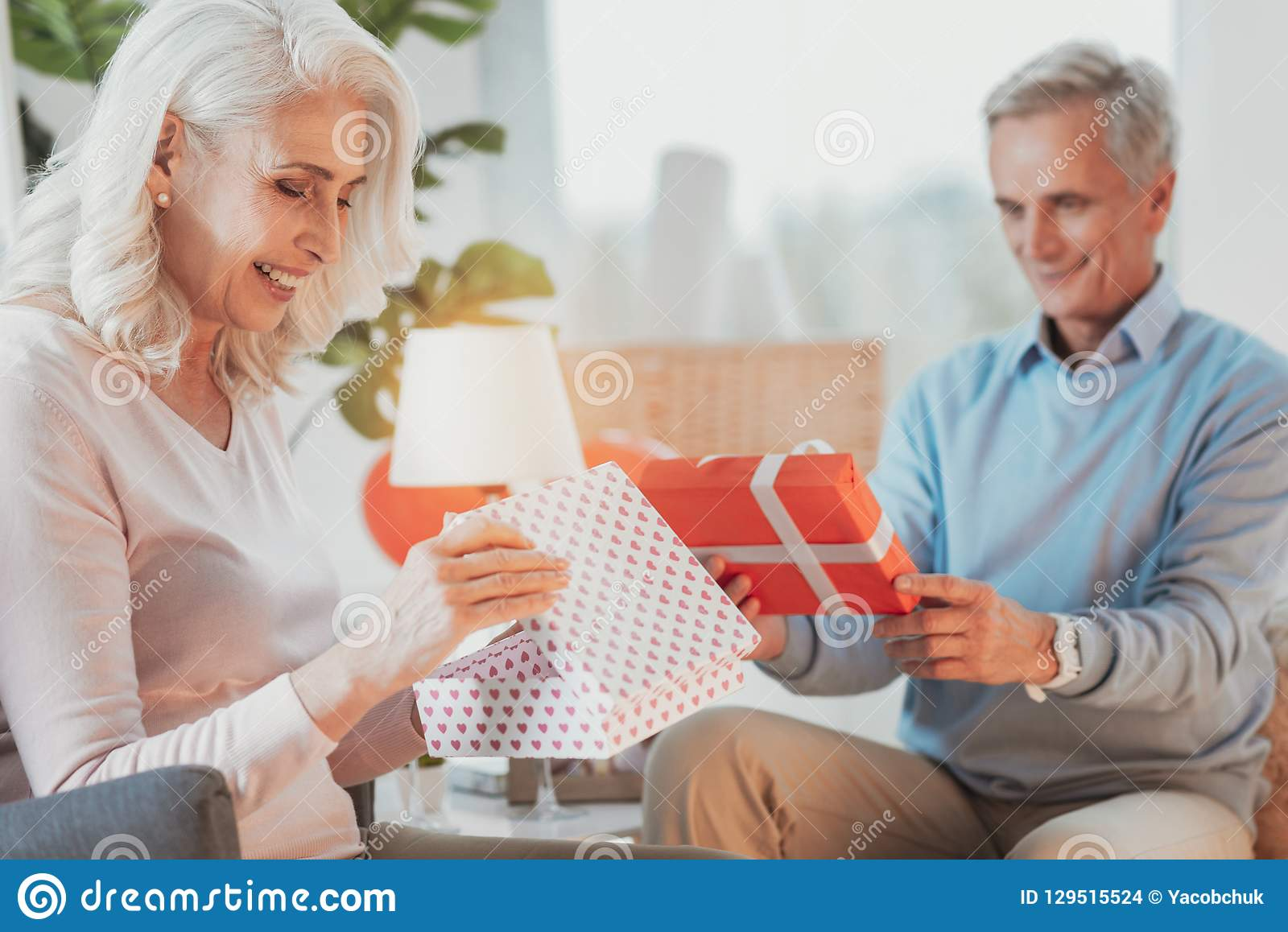 Elderly positive couple their opening gifts