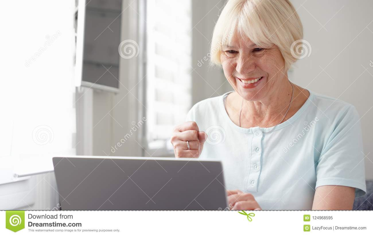 Elderly senior blond woman working on laptop computer at home. Received good news excited and happy