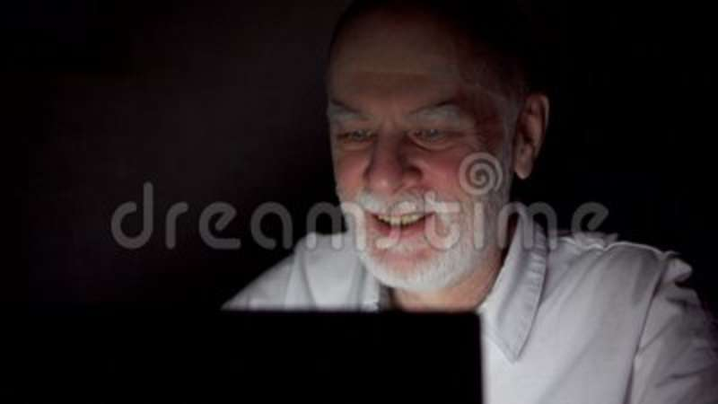 Senior man having video chat via messenger app call on laptop at night   Dark only face illuminated