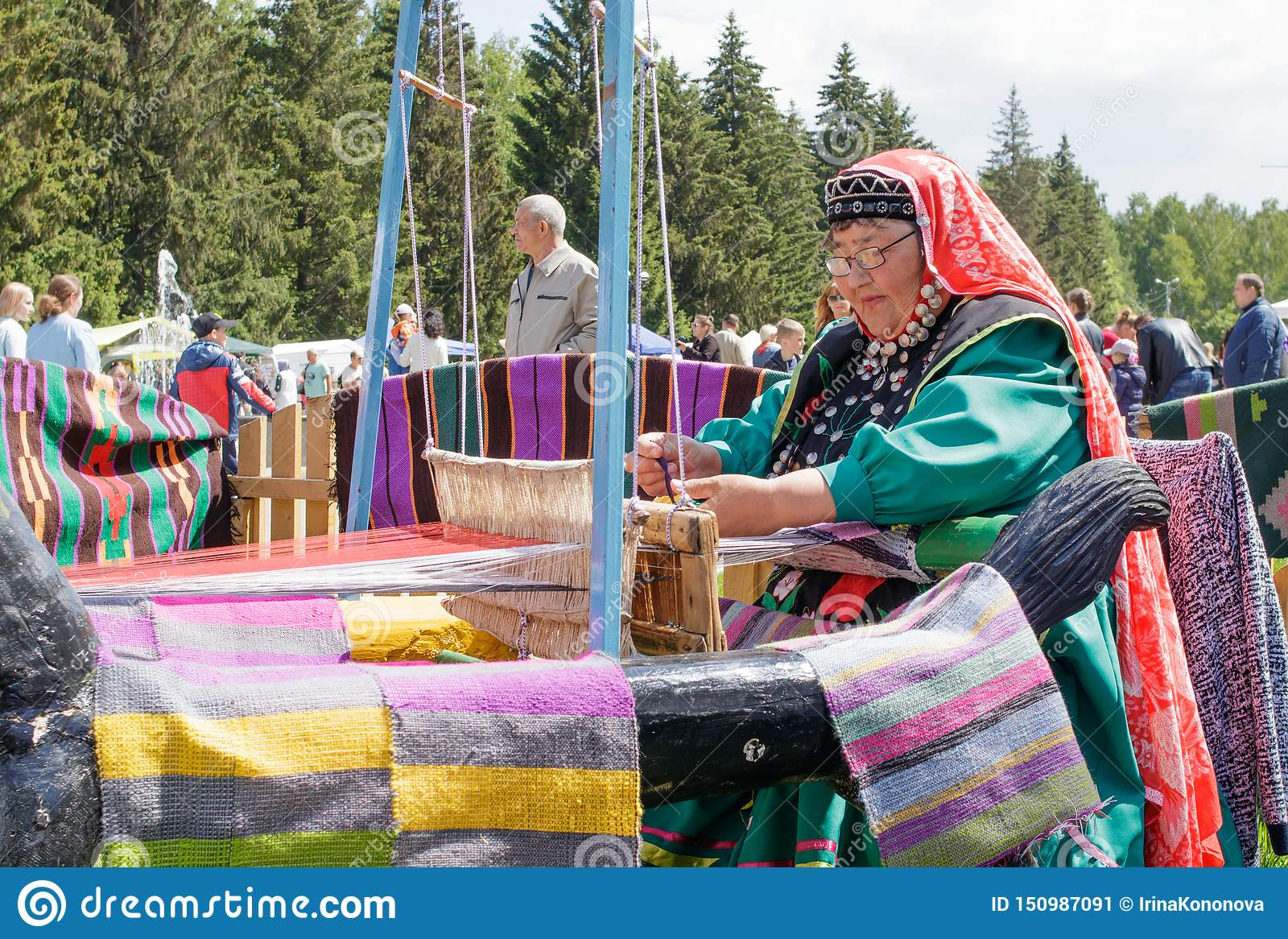An elderly woman in Bashkir clothes is seated at a old wooden oom and weaves a carpet. National holiday Sabantuy in the city park