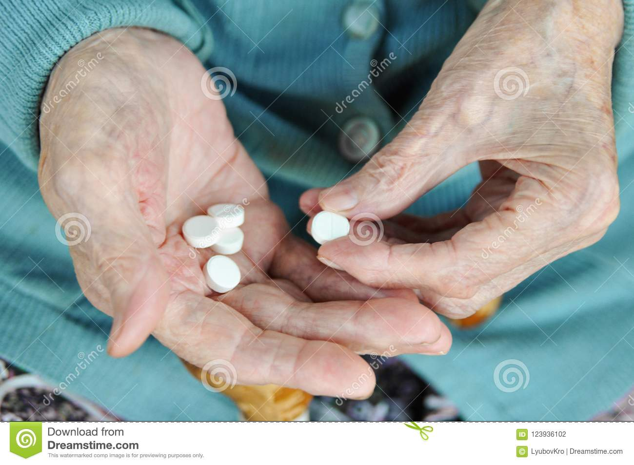 An elderly woman with a cane holding a pill on the street. 90 years. Health. concept illness and healthcare