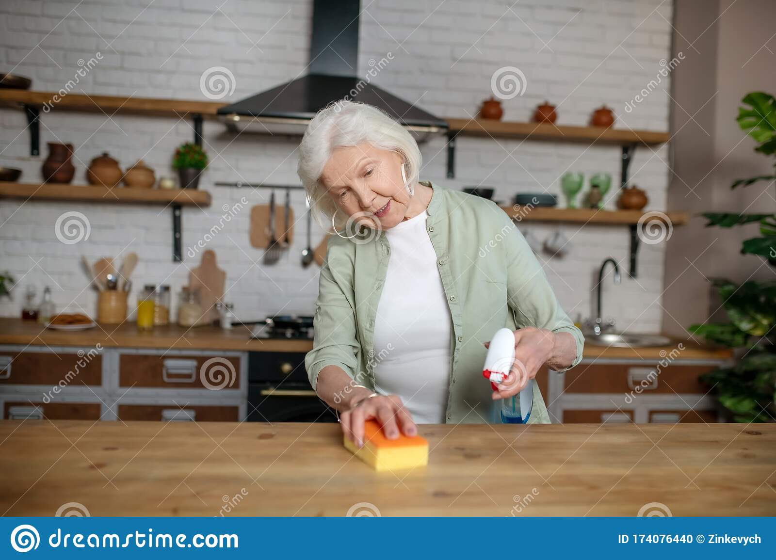 Elderly Woman Cleaning A Table In Her Kitchen Stock Photo ...