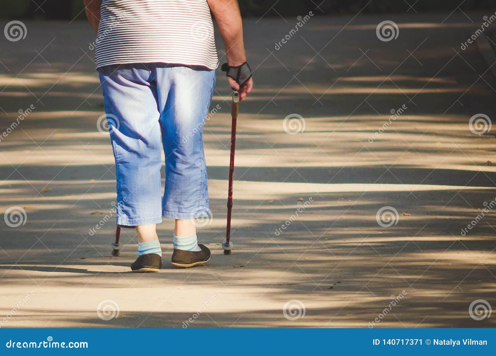 An elderly woman is engaged in Scandinavian walk in the park, Russia