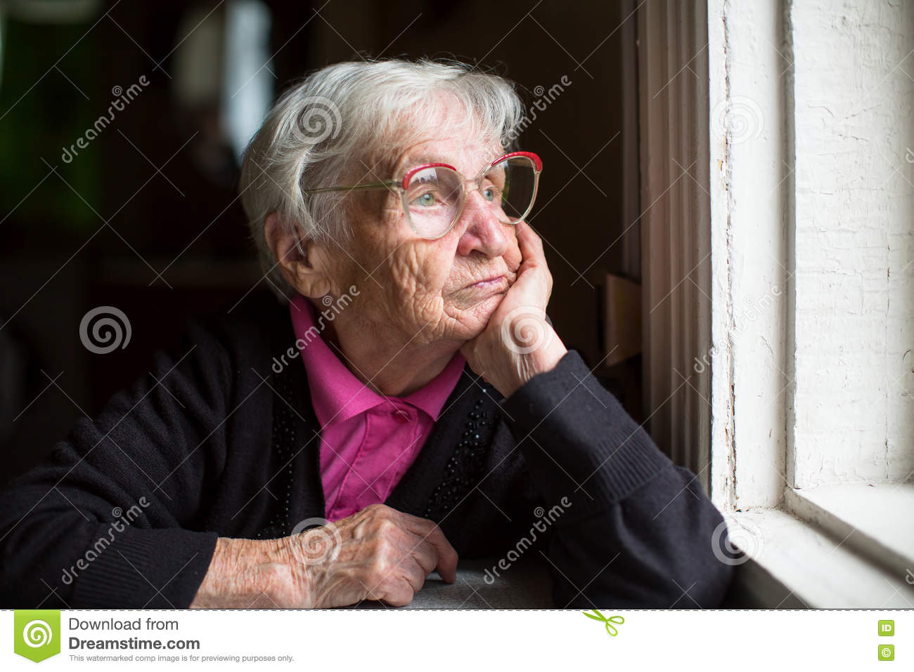 Elderly woman in glasses thoughtfully looking out the window. Loneliness.