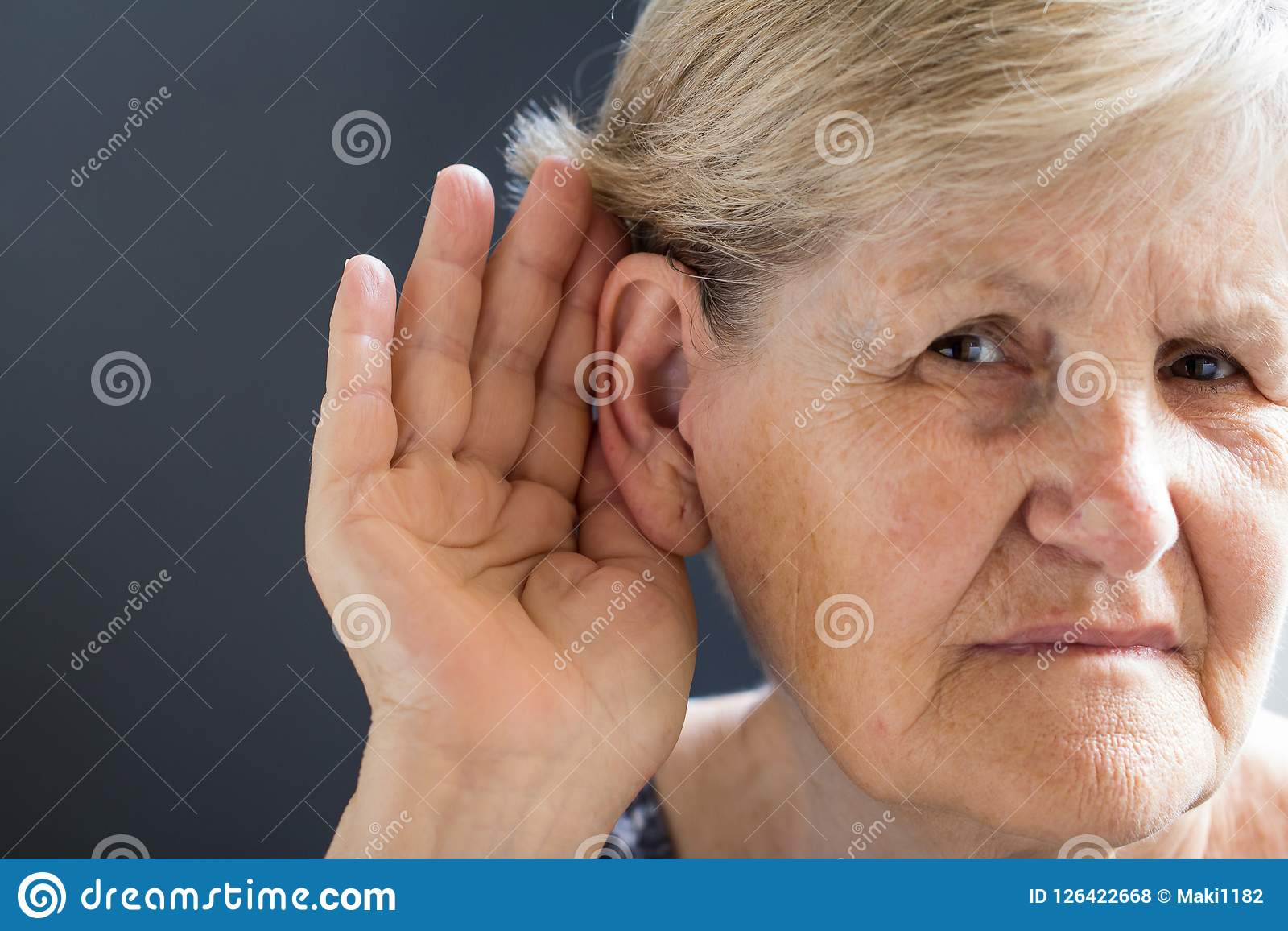 Elderly woman with hearing loss on grey background. Age related