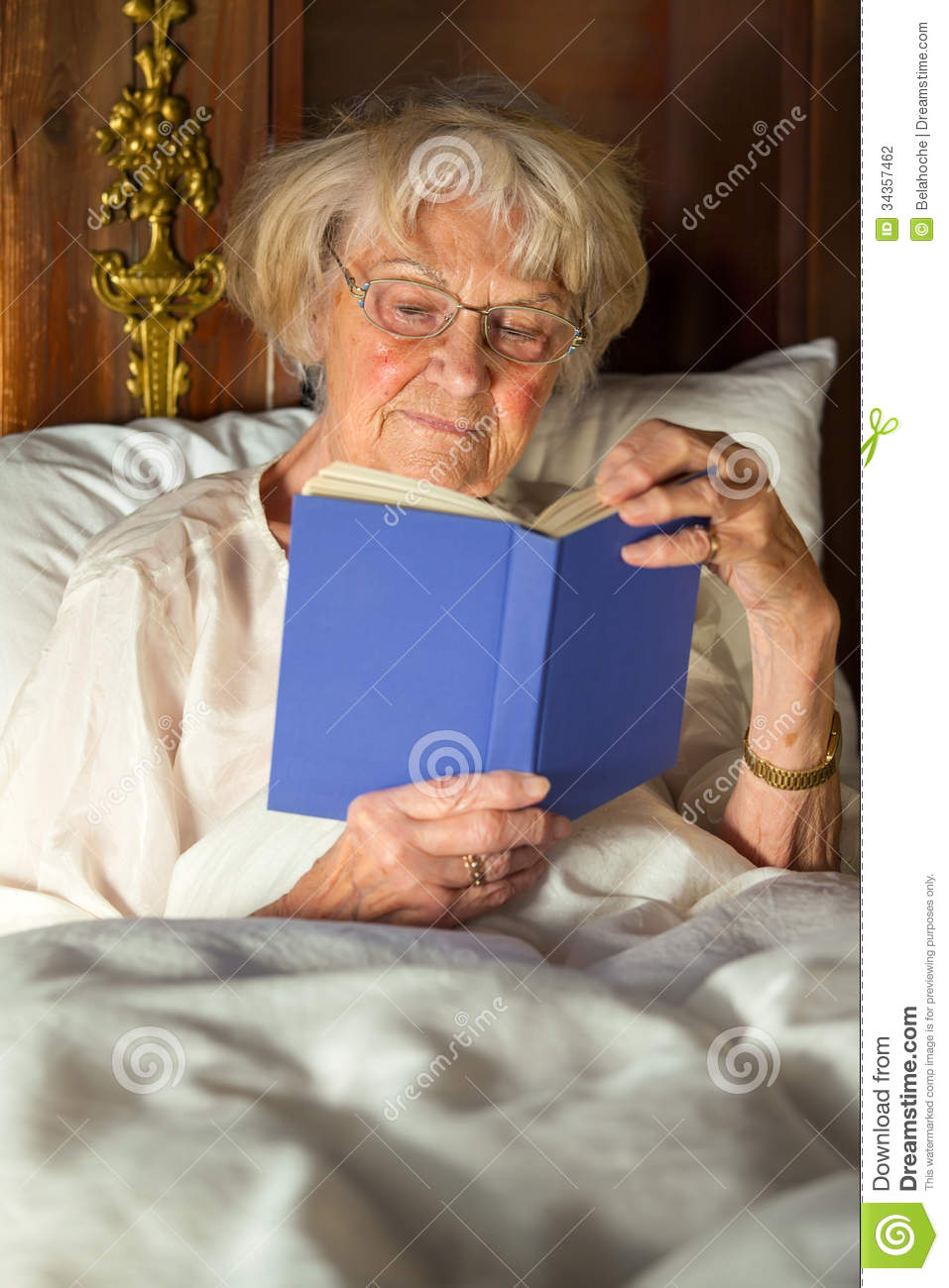 Elderly Woman In Her Nightgown Reading In Bed Stock Photo