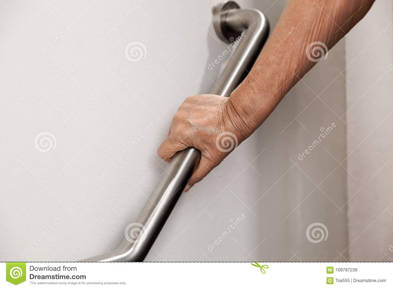 Elderly woman holding on handrail for safety steps