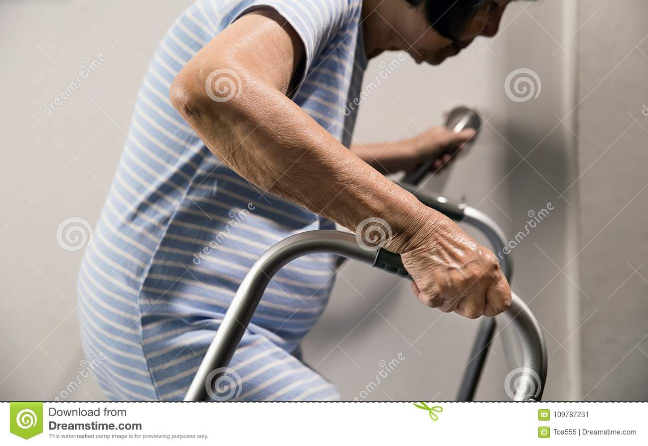 Elderly woman holding on handrail and walker for safety
