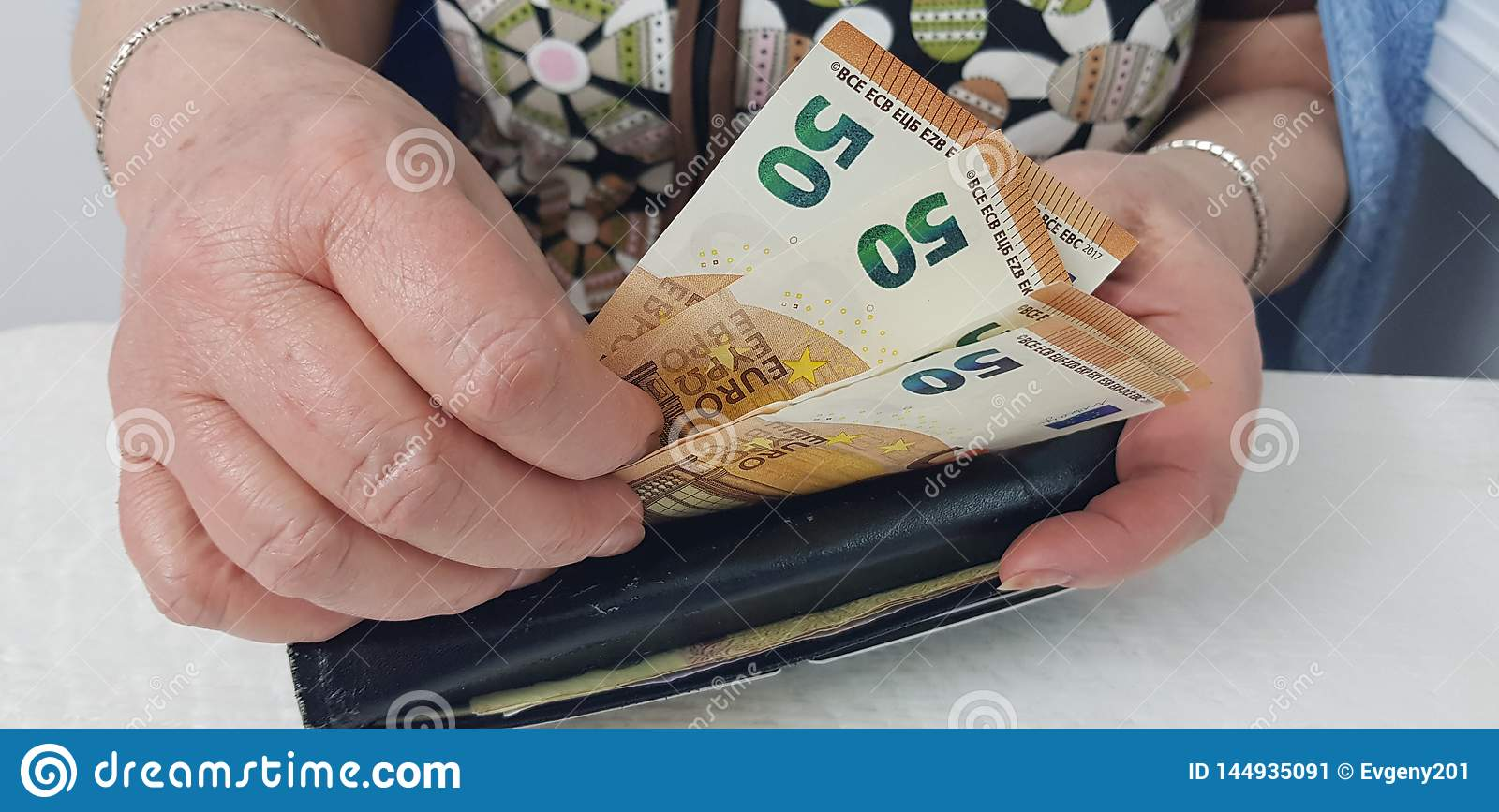 Elderly woman holds in hands euro cash money putting it into wallet