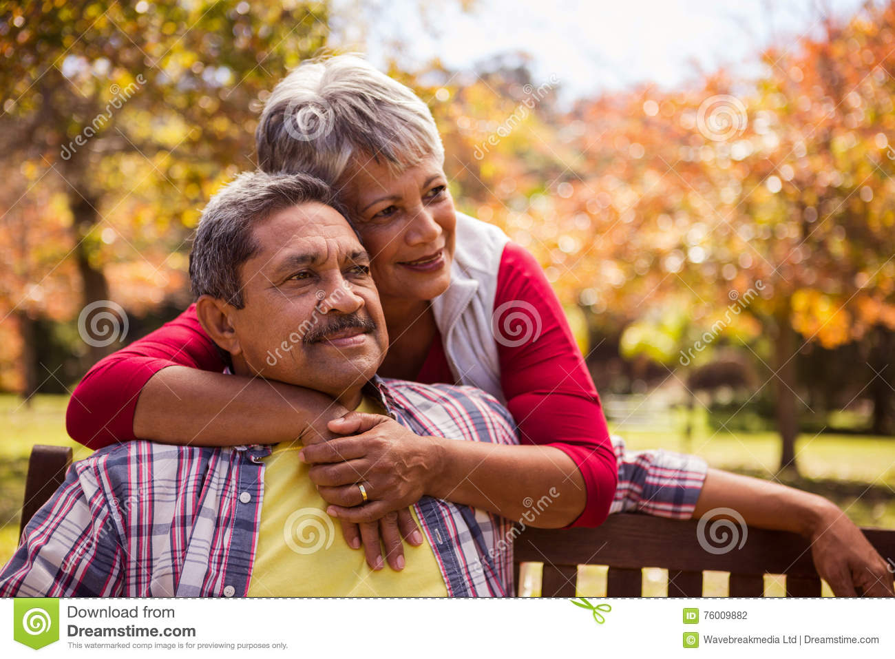 An elderly woman hugs her husband sitting on the bench